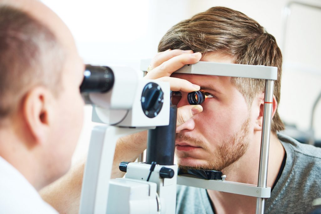 Ophthalmology concept. Male patient under eye vision examination in eyesight ophthalmological correction clinic.